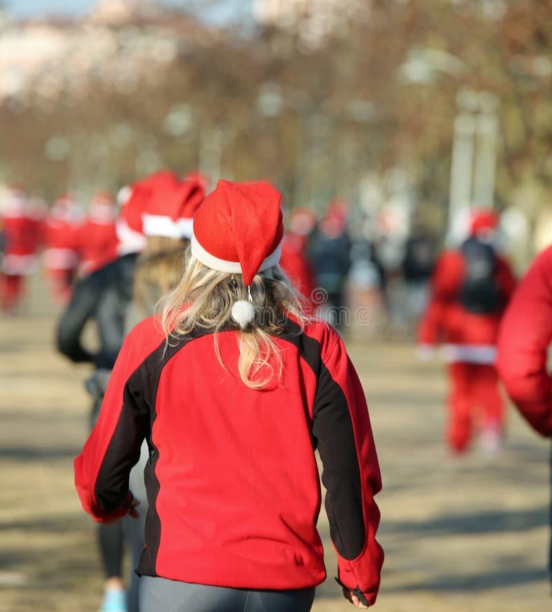 Γυναίκα με τα ξανθά μαλλιά που τρέχουν κατά τη διάρκεια του τρεξίματος Santas σε Χριστό στοκ εικόνες με δικαίωμα ελεύθερης χρήσης