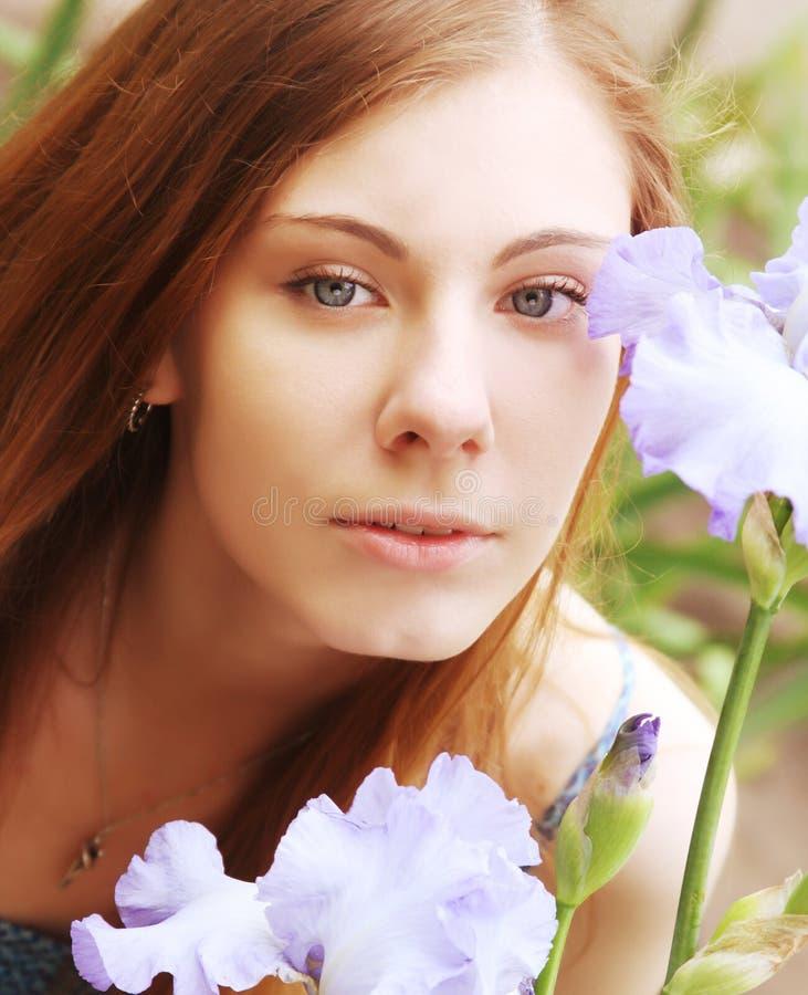 Γυναίκα με τα λουλούδια που θέτουν στο θερινό πάρκο στοκ φωτογραφίες