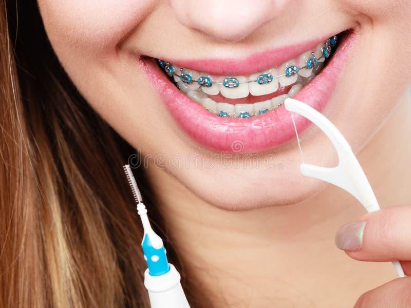 Γυναίκα με τα στηρίγματα που καθαρίζουν τα δόντια με την οδοντόβουρτσα στοκ φωτογραφίες