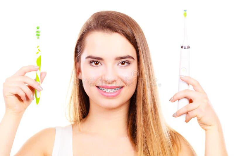 Γυναίκα με τα στηρίγματα που κρατά την ηλεκτρική και παραδοσιακή οδοντόβουρτσα στοκ εικόνες