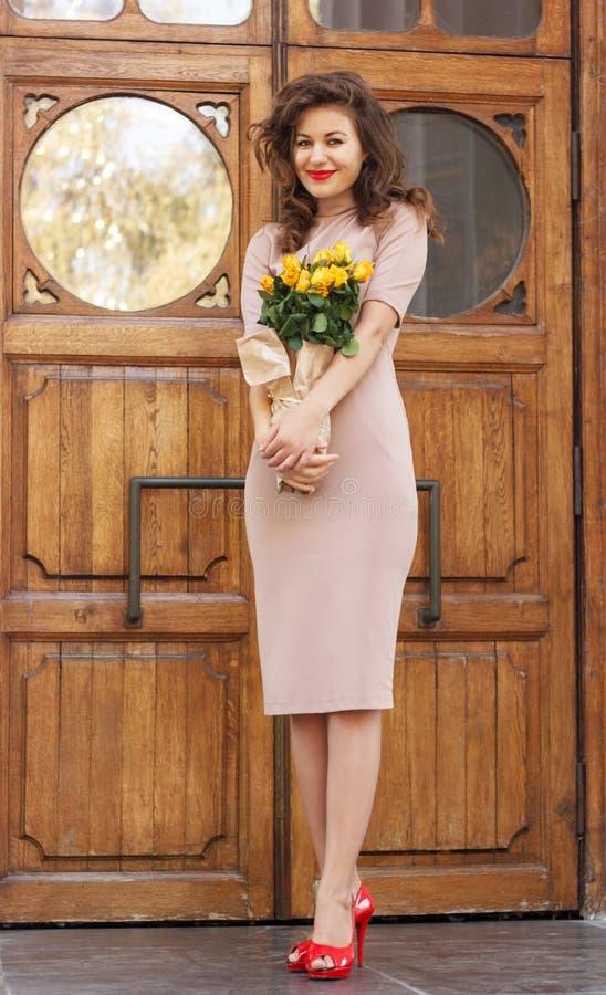 Γυναίκα με τα τριαντάφυλλα που στέκονται κοντά στην αρχαία πόρτα στοκ φωτογραφίες με δικαίωμα ελεύθερης χρήσης