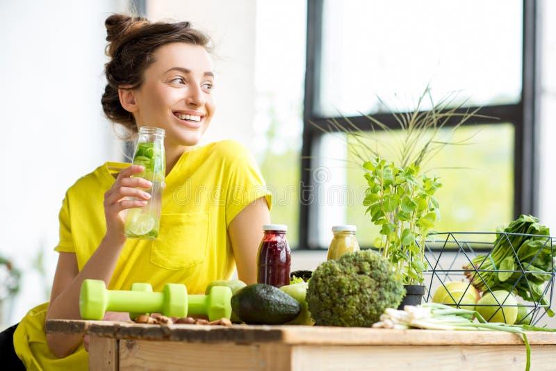 Γυναίκα με τα υγιή τρόφιμα στο εσωτερικό στοκ εικόνες