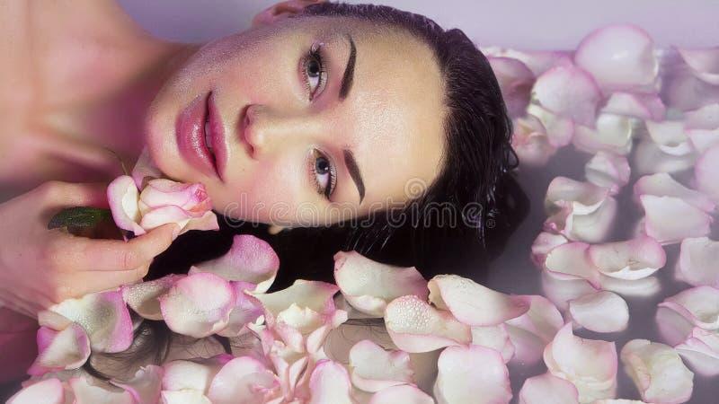 Γυναίκα με τα φρέσκα ροδαλά πέταλα και το ρόδινο μπουμπούκι τριαντάφυλλου Φυσικός αυξήθηκε wate στοκ φωτογραφία