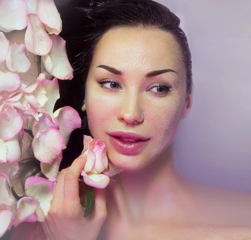 Γυναίκα με τα φρέσκα ροδαλά πέταλα και το ρόδινο μπουμπούκι τριαντάφυλλου Φυσικός αυξήθηκε wate στοκ εικόνες