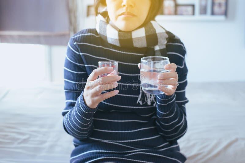 Γυναίκα με τα χάπια ή τις κάψες σε διαθεσιμότητα και ένα ποτήρι του νερού στοκ φωτογραφία με δικαίωμα ελεύθερης χρήσης