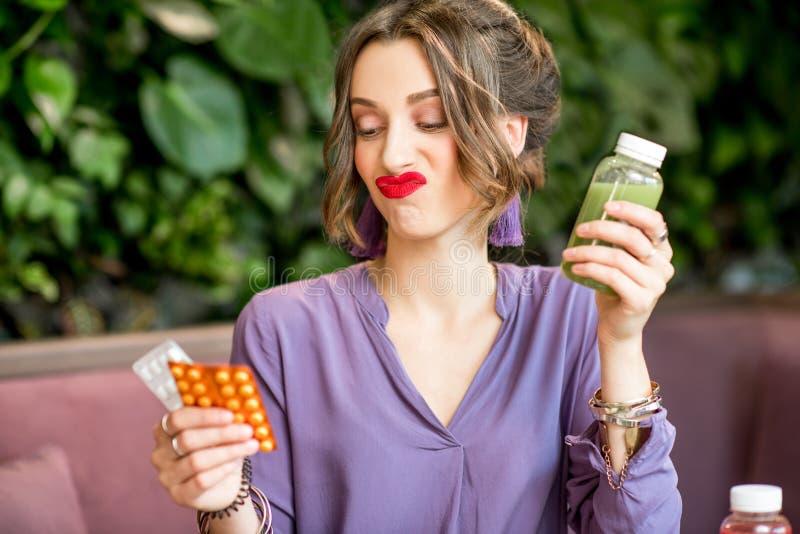Γυναίκα με τα χάπια και τα υγιή τρόφιμα στοκ φωτογραφία
