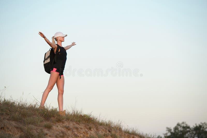 Γυναίκα με τα χέρια που στέκονται επάνω στην κορυφή του λόφου Ταξίδι, vac στοκ εικόνες