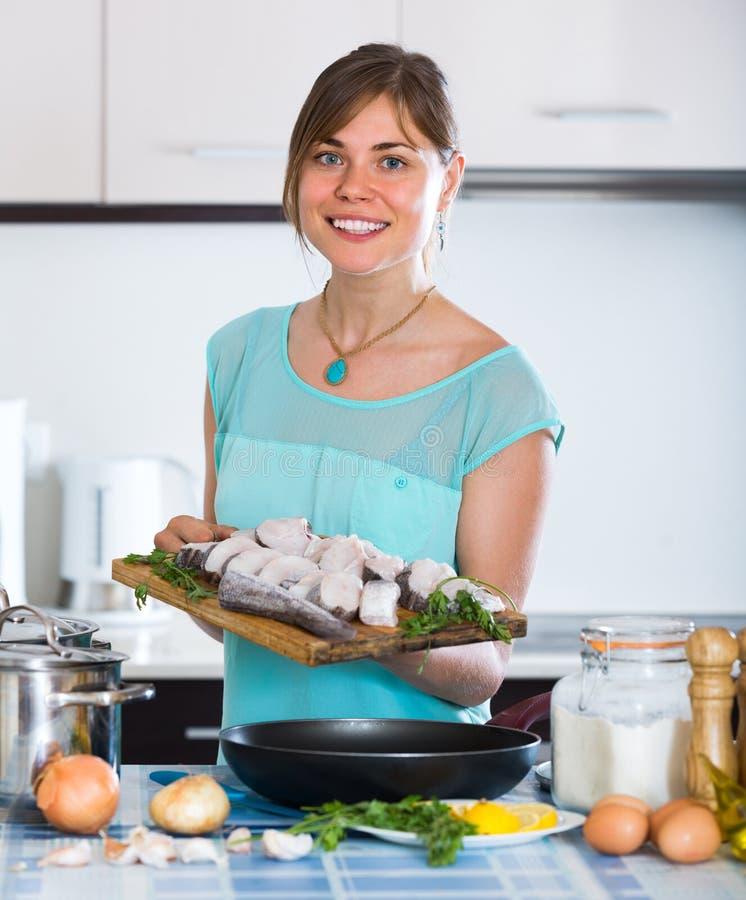 Γυναίκα με τα ψάρια και τηγανίζοντας τηγάνι στην κουζίνα στοκ φωτογραφίες με δικαίωμα ελεύθερης χρήσης