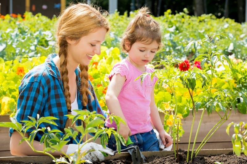 Γυναίκα με την λίγη κόρη στον κήπο στοκ εικόνα με δικαίωμα ελεύθερης χρήσης