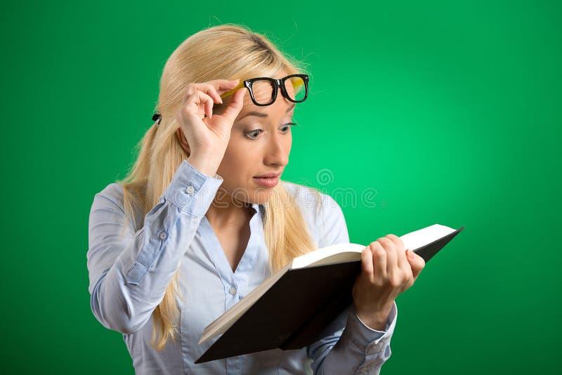 Γυναίκα με την ανάγνωση γυαλιών που εξετάζει το βιβλίο που συγκλονίζεται έκπληκτη στοκ εικόνες