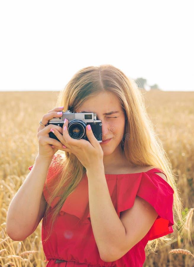 Γυναίκα με την αναδρομική κάμερα φωτογραφιών Υπαίθρια έννοια τρόπου ζωής ταξιδιού μόδας στοκ εικόνα