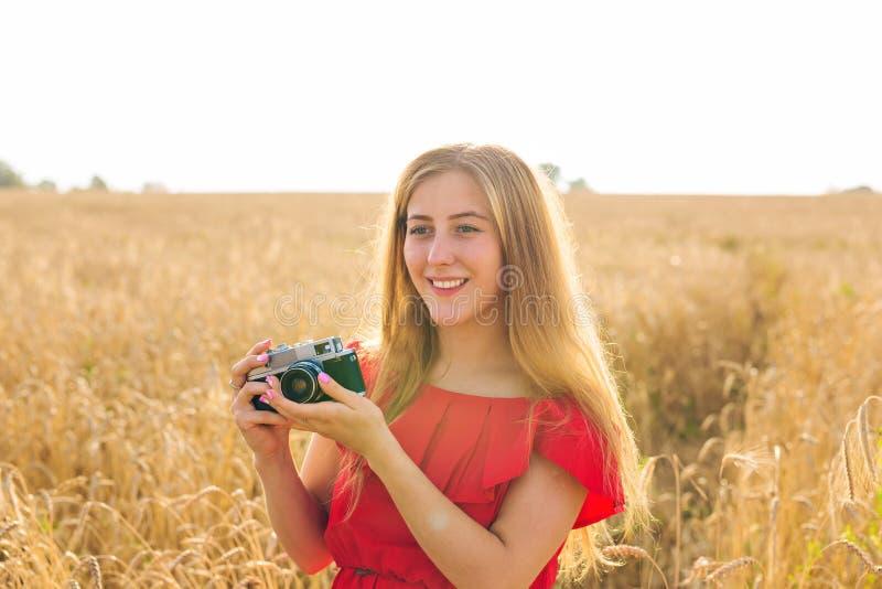 Γυναίκα με την αναδρομική κάμερα φωτογραφιών Υπαίθρια έννοια τρόπου ζωής ταξιδιού μόδας στοκ φωτογραφία