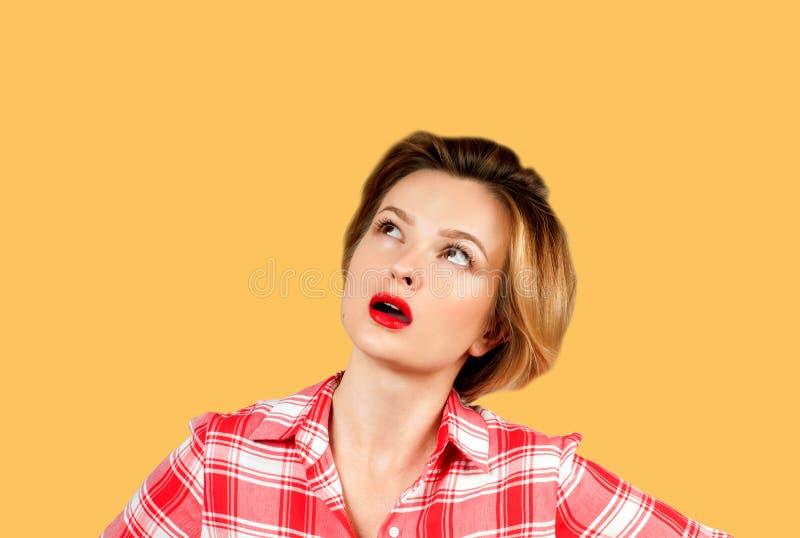 Γυναίκα με την επερώτηση της έκφρασης που ανατρέχει στο κίτρινο υπόβαθρο στοκ φωτογραφίες με δικαίωμα ελεύθερης χρήσης