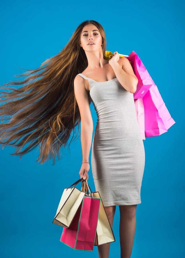Γυναίκα με την ευτυχή τσάντα αγορών λαβής προσώπου κοντά στον μπλε τοίχο στοκ φωτογραφία με δικαίωμα ελεύθερης χρήσης