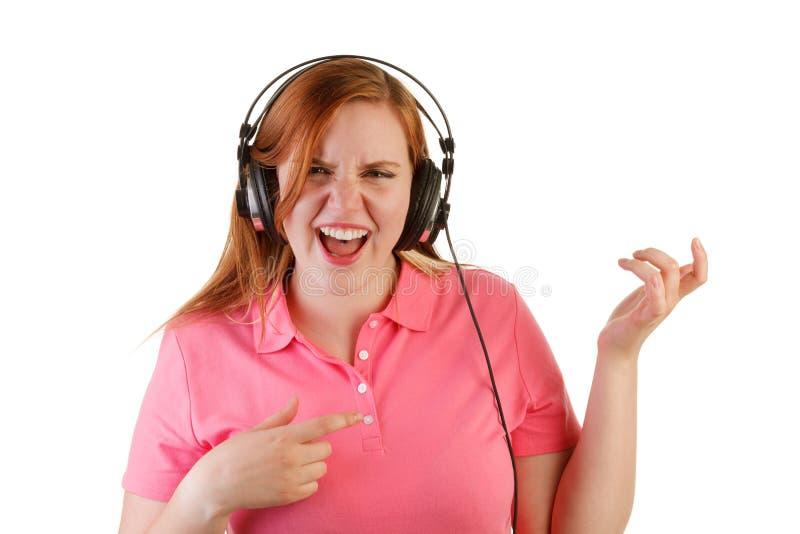 Γυναίκα με την κιθάρα αέρα παιχνιδιού ακουστικών στοκ εικόνες