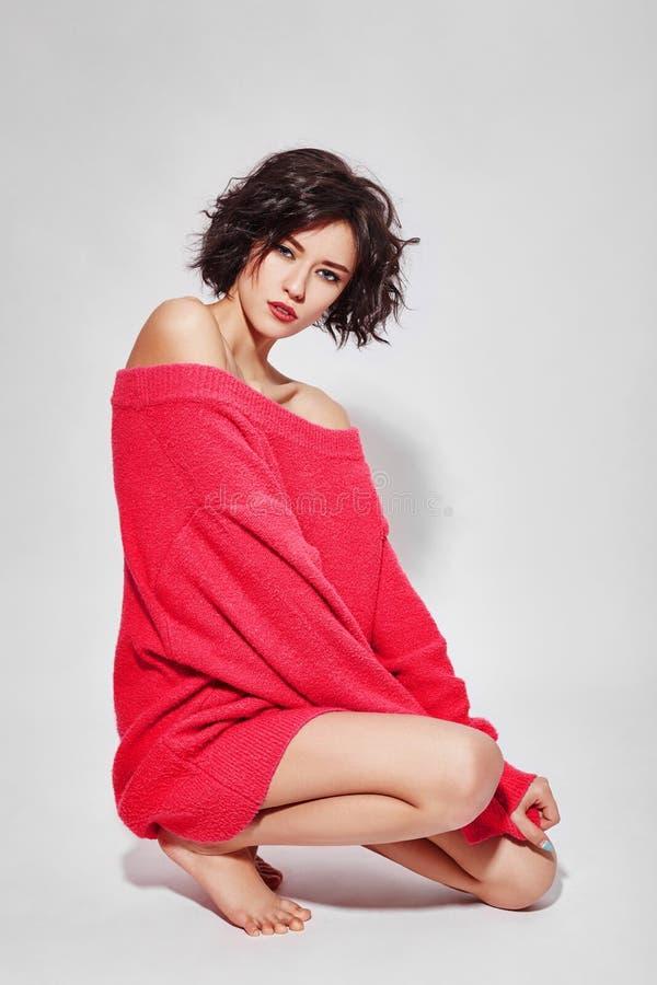 γυναίκα με την κοντή τρίχα που κόβεται στο ρόδινο κόκκινο πουλόβερ στο άσπρο υπόβαθρο Το τέλειο κορίτσι με υγρό η σκοτεινή τρίχα  στοκ εικόνες με δικαίωμα ελεύθερης χρήσης