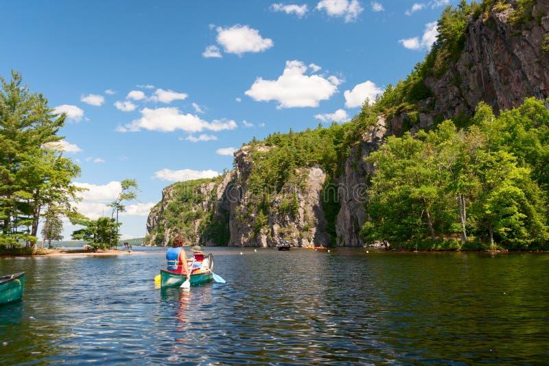 Γυναίκα με την κωπηλασία σε κανό παιδιών στη λίμνη στοκ φωτογραφία
