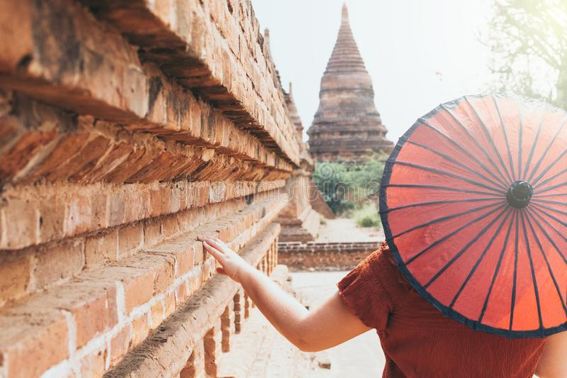 Γυναίκα με την κόκκινη ομπρέλα που αγνοεί την παγόδα και το ναό αρχαίου Bagan στο Μιανμάρ στοκ εικόνες