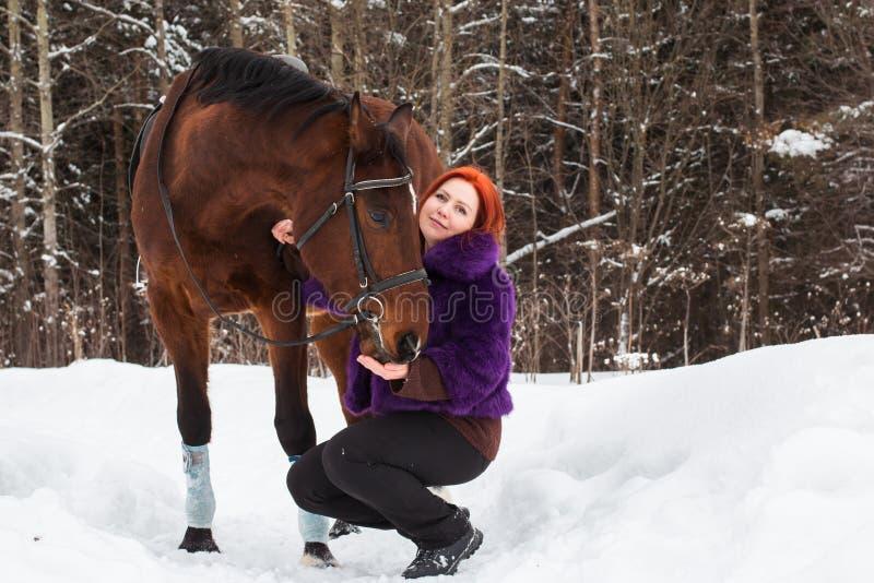 Γυναίκα με την κόκκινη τρίχα και το μεγάλο άλογο υπαίθριες το χειμώνα στοκ φωτογραφίες