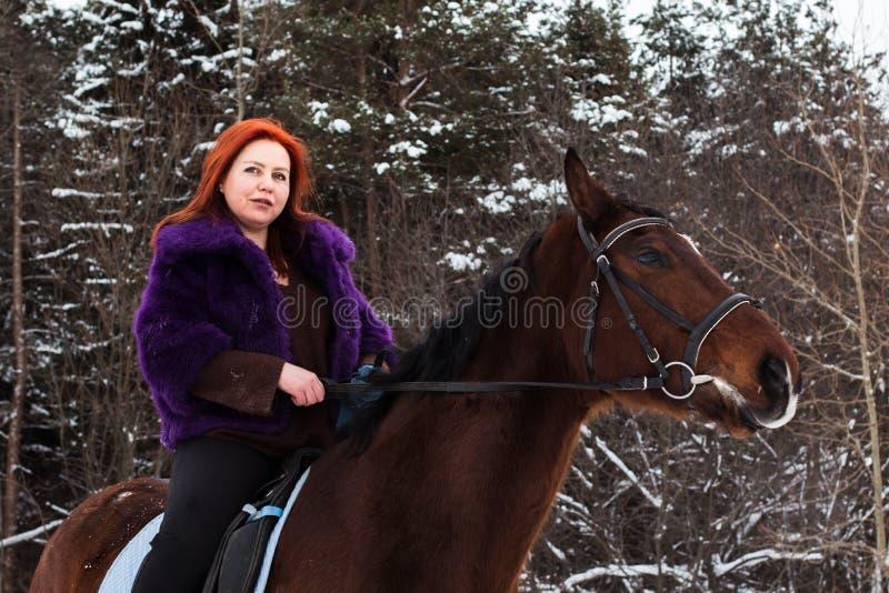 Γυναίκα με την κόκκινη τρίχα και το μεγάλο άλογο υπαίθριες το χειμώνα στοκ εικόνα με δικαίωμα ελεύθερης χρήσης