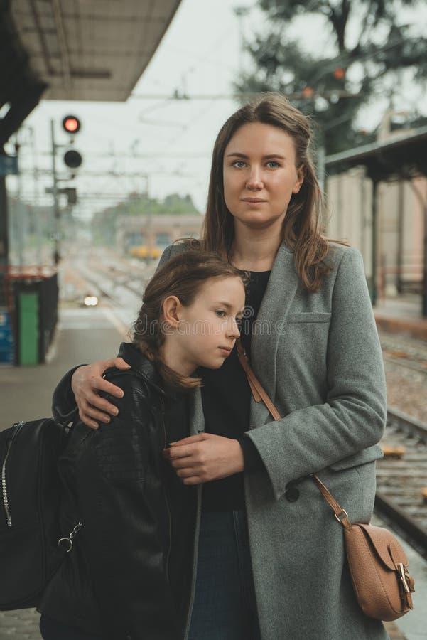 Γυναίκα με την κόρη της στο σιδηροδρομικό σταθμό στοκ φωτογραφία