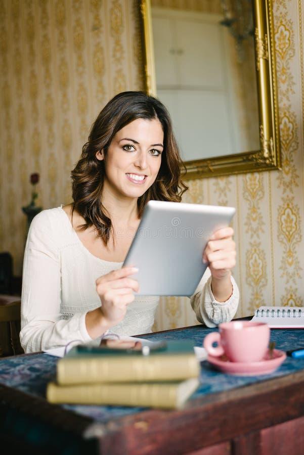 Γυναίκα με την ψηφιακή ταμπλέτα που λειτουργεί στο εκλεκτής ποιότητας σπίτι στοκ φωτογραφία με δικαίωμα ελεύθερης χρήσης