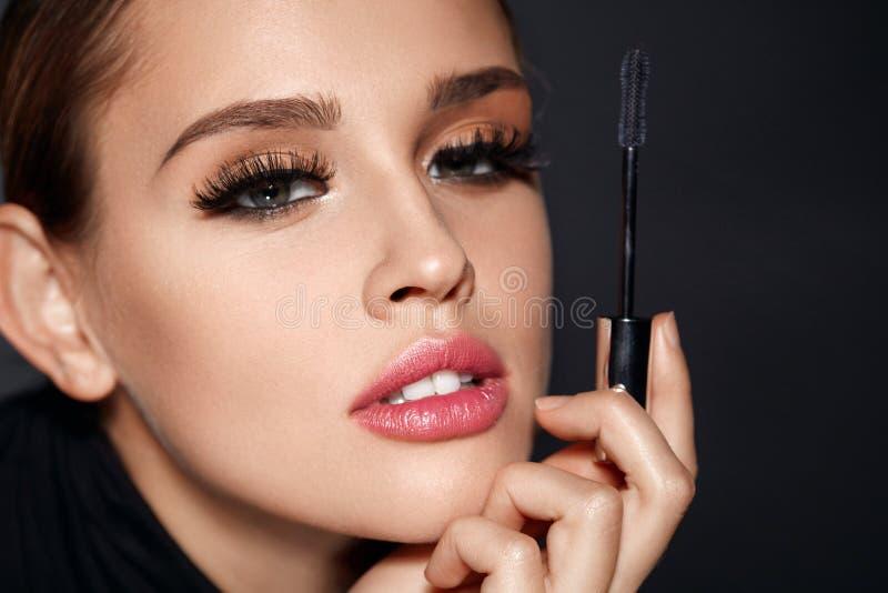 _ Γυναίκα με την όμορφη βούρτσα προσώπου και Mascara υπό εξέταση στοκ εικόνα