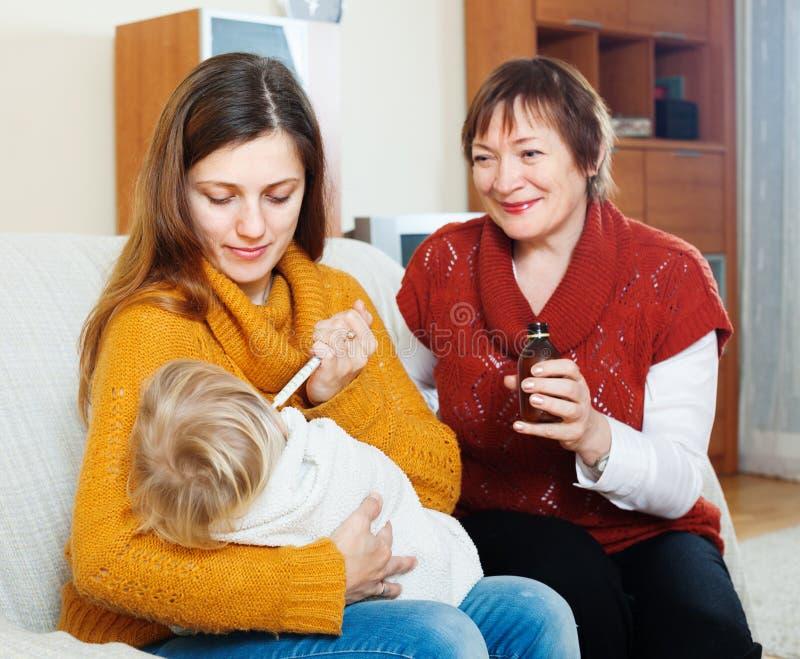Γυναίκα με την ώριμη μητέρα που δίνει το υγρό φάρμακο στο μικρό παιδί στοκ φωτογραφίες