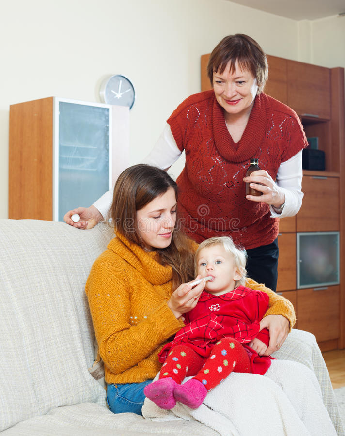 Γυναίκα με την ώριμη μητέρα που δίνει το φάρμακο στο μωρό στοκ εικόνες