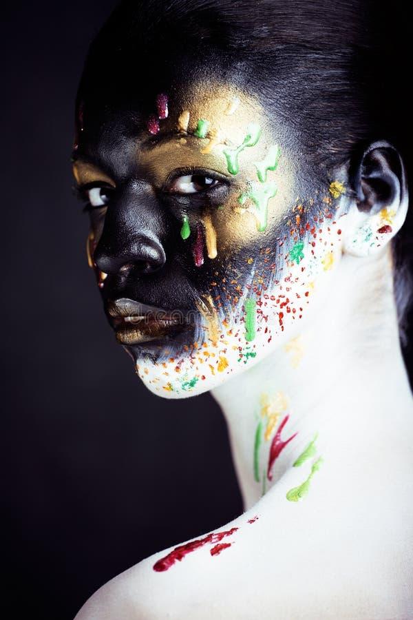 Γυναίκα με τη δημιουργική κινηματογράφηση σε πρώτο πλάνο makeup όπως τις πτώσεις των χρωμάτων, facepai στοκ εικόνα