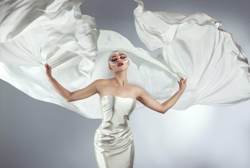 Γυναίκα με τη δημιουργική σύνθεση σε ένα άσπρο πέταγμα υφασμάτων Ένα κορίτσι που κρατά ένα πετώντας άσπρο ύφασμα στοκ εικόνες με δικαίωμα ελεύθερης χρήσης