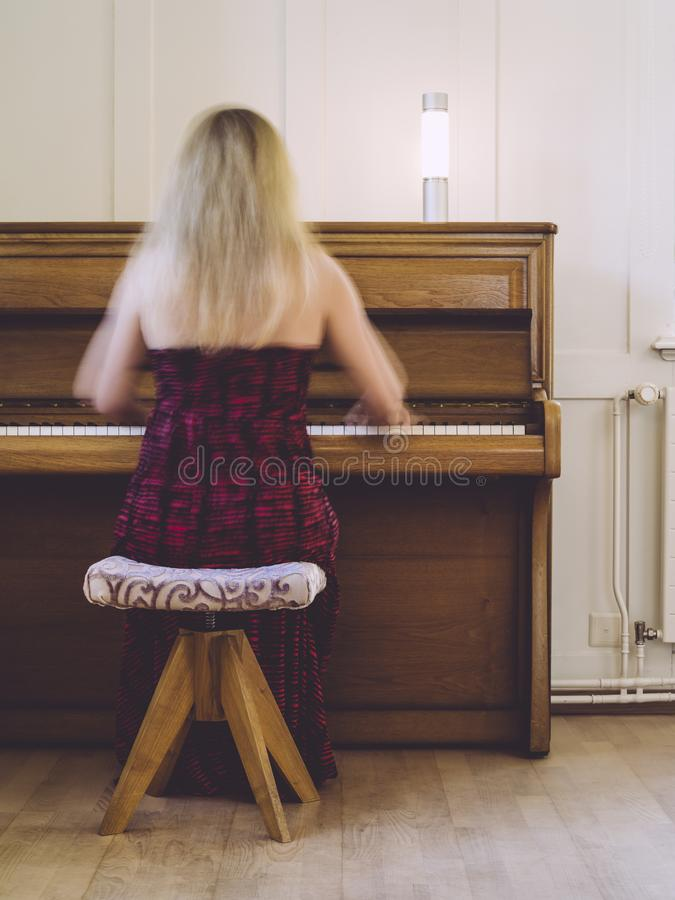 Γυναίκα με τη θαμπάδα κινήσεων που παίζει το πιάνο στοκ φωτογραφία με δικαίωμα ελεύθερης χρήσης
