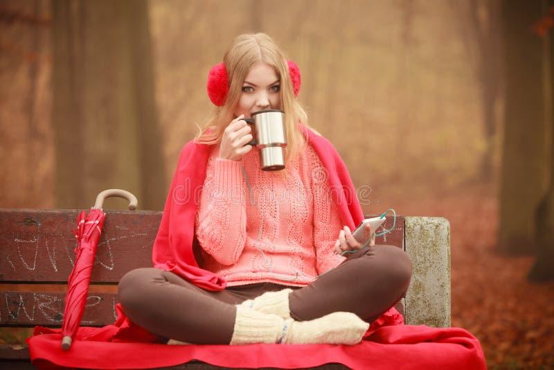 Γυναίκα με τη θερμική μουσική ακούσματος κουπών στο τοπίο φθινοπώρου στοκ φωτογραφία με δικαίωμα ελεύθερης χρήσης