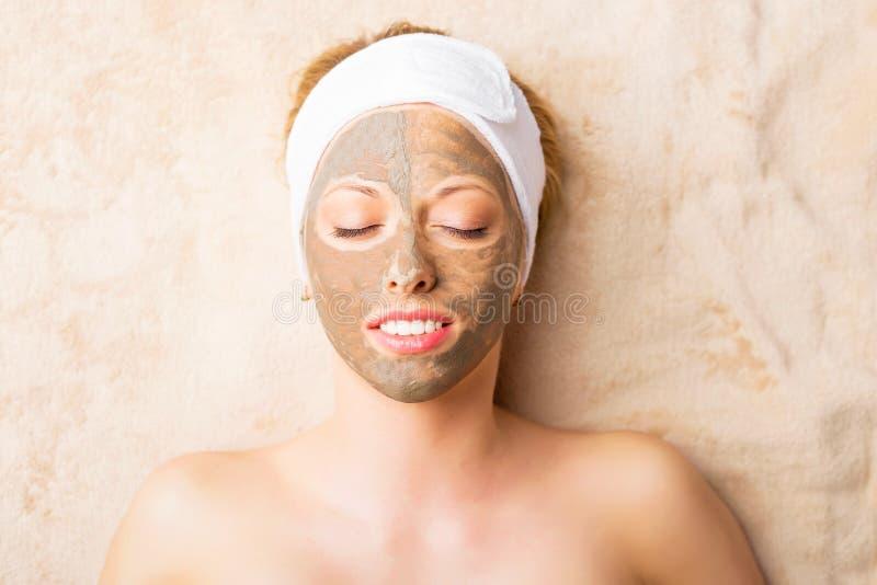 Γυναίκα με τη μάσκα αργίλου στο πρόσωπό της στοκ φωτογραφίες