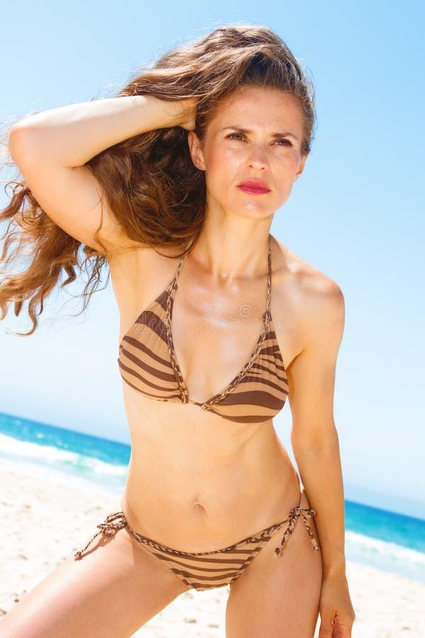 Γυναίκα με τη μακριά τρίχα brunette στην ακτή που εξετάζει την απόσταση στοκ εικόνες
