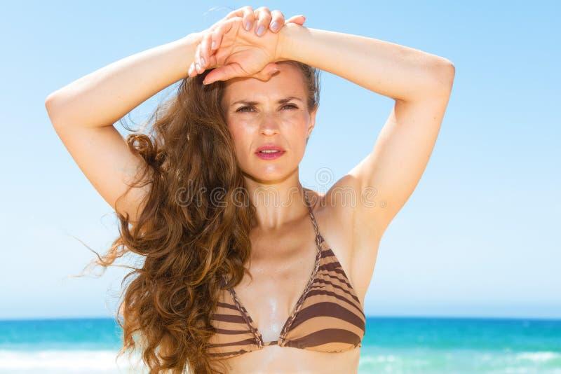Γυναίκα με τη μακριά τρίχα brunette στην ακτή που εξετάζει την απόσταση στοκ φωτογραφία
