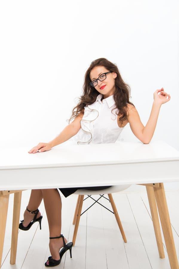 Γυναίκα με τη μακρυμάλλη άσπρη μπλούζα Ο δάσκαλος με τα γυαλιά φαίνεται ελκυστικός Ο σαγηνευτικός διοικητής γραφείων κάθεται στον στοκ εικόνες
