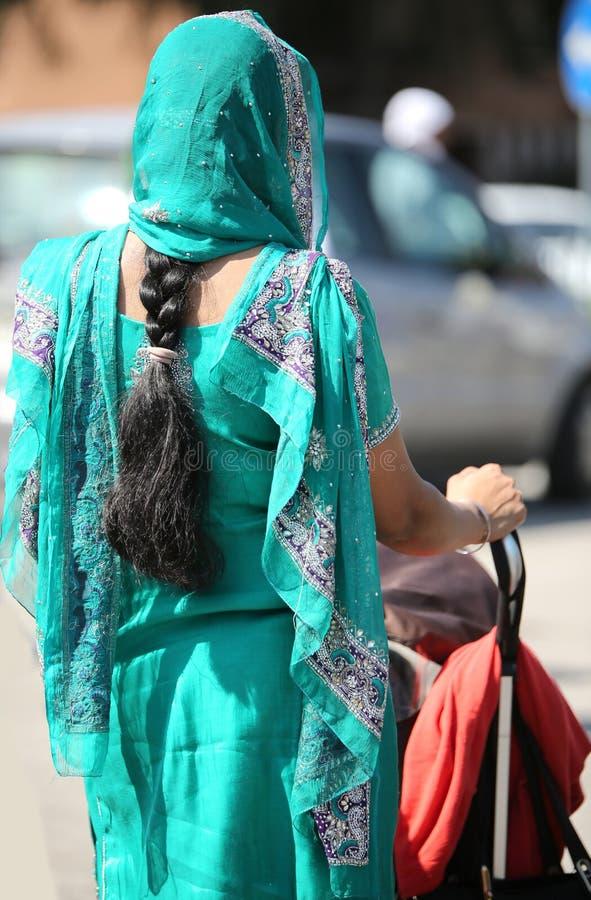 γυναίκα με τη μαύρη πλεξούδα τρίχας του πέπλου ωθώντας έναν περιπατητή στοκ εικόνα με δικαίωμα ελεύθερης χρήσης