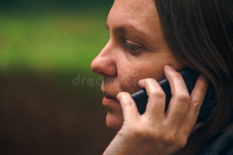 Γυναίκα με τη σοβαρή έκφραση προσώπου που μιλά στο τηλέφωνο στο πάρκο στοκ φωτογραφία