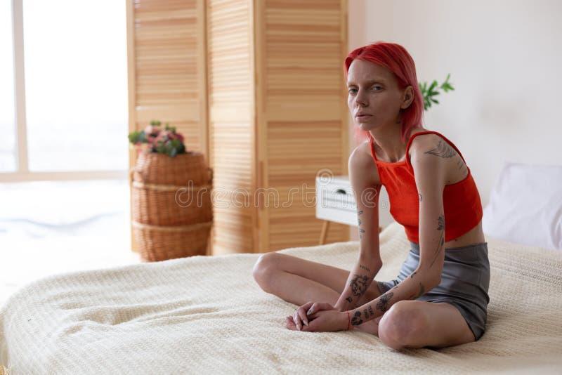 Γυναίκα με τη συνεδρίαση βουλιμίας στο κρεβάτι που αισθάνεται κακή και μόνη στοκ φωτογραφίες με δικαίωμα ελεύθερης χρήσης