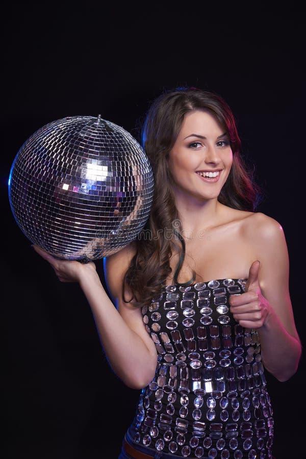 Γυναίκα με τη σφαίρα disco που παρουσιάζει αντίχειρα στοκ φωτογραφία με δικαίωμα ελεύθερης χρήσης