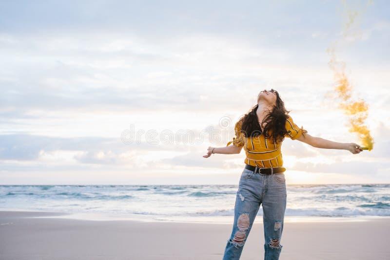 Γυναίκα με τη χειροβομβίδα καπνού στην παραλία στοκ εικόνες
