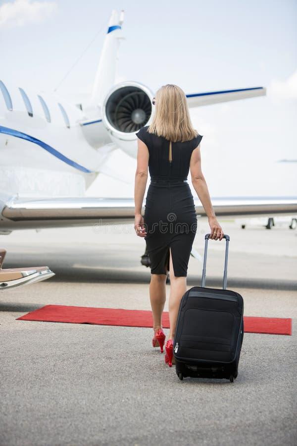 Γυναίκα με τις αποσκευές που περπατά προς το ιδιωτικό αεριωθούμενο αεροπλάνο στοκ φωτογραφία με δικαίωμα ελεύθερης χρήσης