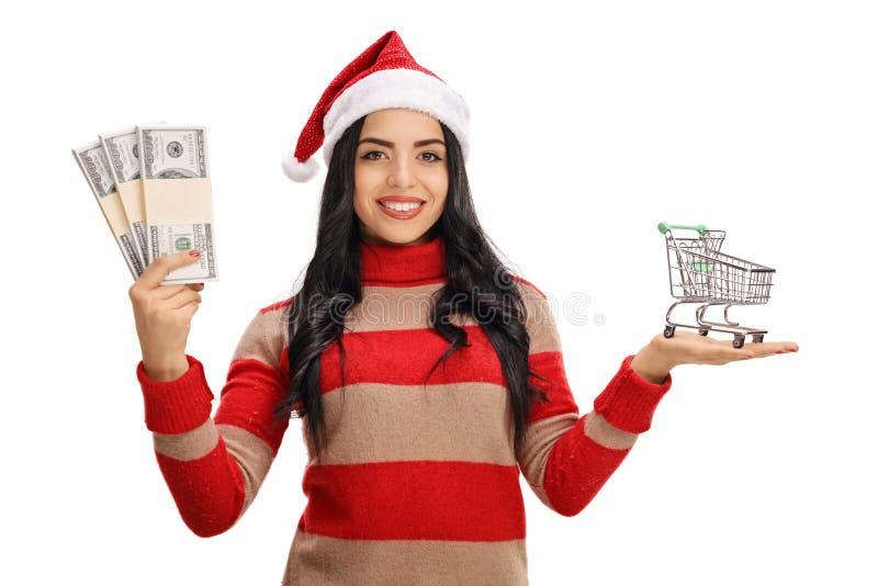 Γυναίκα με τις δέσμες χρημάτων εκμετάλλευσης καπέλων Χριστουγέννων και το κάρρο αγορών στοκ φωτογραφία