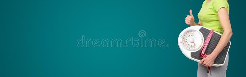 Γυναίκα με τις κλίμακες στο πράσινο υπόβαθρο στοκ εικόνες με δικαίωμα ελεύθερης χρήσης