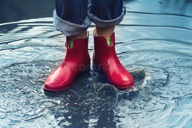 Γυναίκα με τις κόκκινες κοντές μπότες που στέκονται σε μια λακκούβα του νερού βροχής στοκ εικόνες