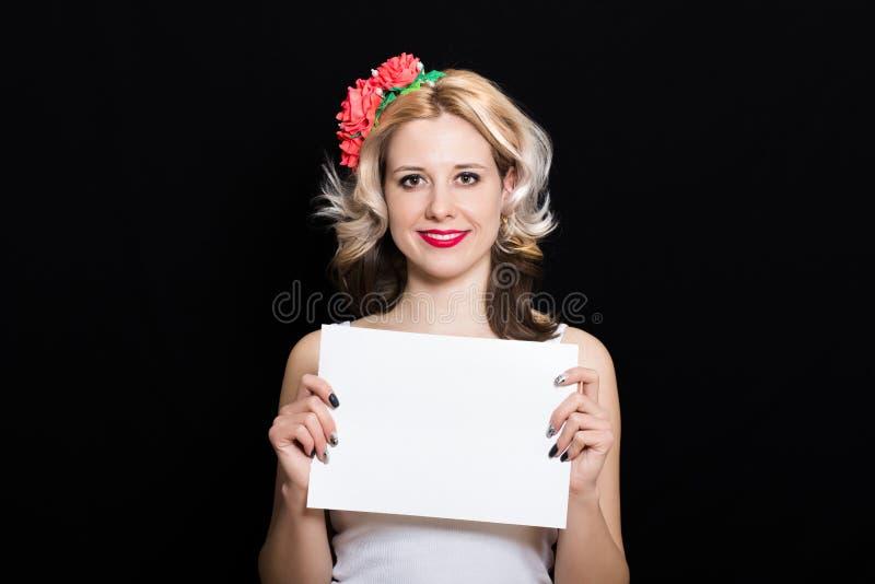 Γυναίκα με τις ξανθές μπούκλες και κόκκινο κραγιόν στο πλαίσιο με το κόκκινο κράτημα λουλουδιών στοκ φωτογραφίες