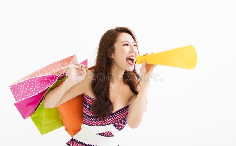 Γυναίκα με τις τσάντες αγορών και κράτημα megaphone στοκ εικόνα