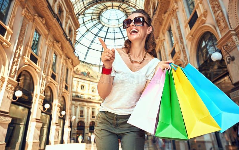 Γυναίκα με τις τσάντες αγορών σε Galleria που δείχνει σε κάτι στοκ εικόνα
