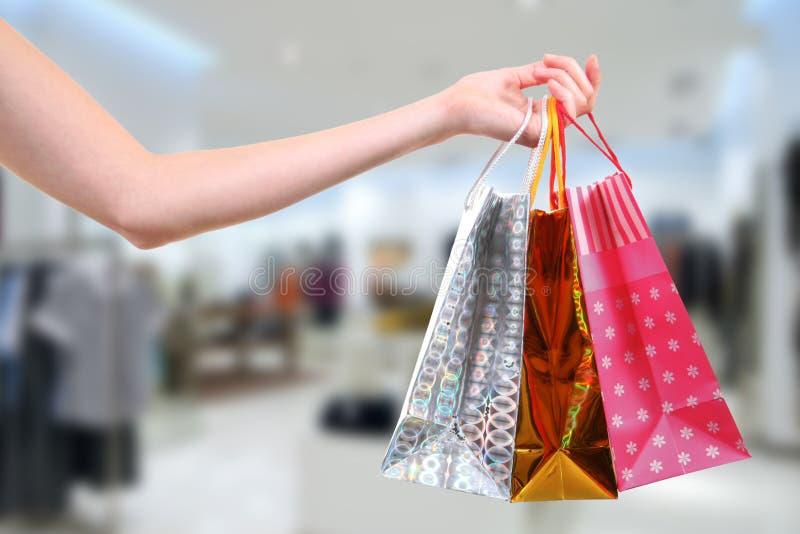 Γυναίκα με τις τσάντες αγορών στο κατάστημα ενδυμάτων στοκ εικόνες με δικαίωμα ελεύθερης χρήσης